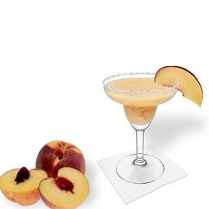 Pfirsich Margarita im Margarita-Glas dekoriert mit einem Stück Pfirsich und Zucker- oder Salzrand. Die beste Art Frozen Peach Margarita zu servieren.